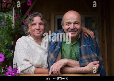 Cheerful senior couple enjoying life at countryside house - Stock Photo