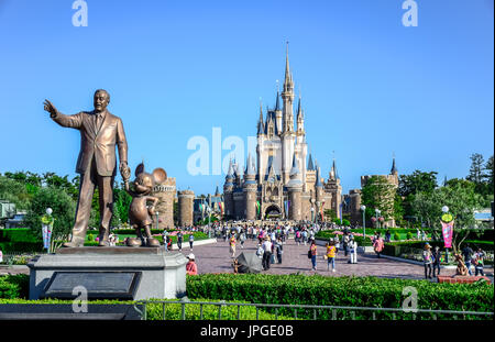 Walt Disney statue holding Mickey Mouse's hand with view of Cinderella Castle in the background, Tokyo Disneyland - Stock Photo