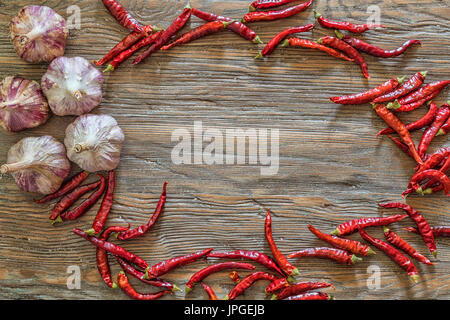 Organic garlic and hot peppers on old wooden table background. - Stock Photo