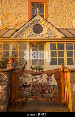 Handmade gate with carved figures on a house in Lower Largo, Fife, SCotland. - Stock Photo