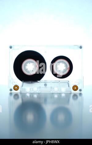 Old audio cassette being backlit on a white background. Retro and vintage theme - Stock Photo