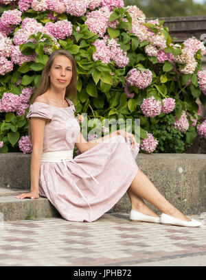 Portrait of a beautiful woman in pink dress sits on a stone staircase on a background of flowers - Stock Photo