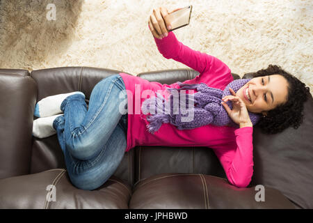 Beautiful girl with short curly hair is taking a selfie with cellphone to post on social media. She is lying in - Stock Photo