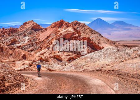 Female cyclist traveling on the road through the famous Valle the la Luna near San Pedro de Atacama, Chile, South - Stock Photo