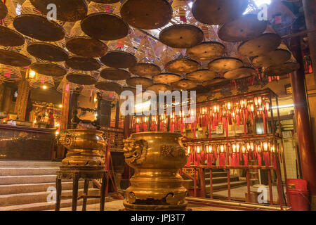 Gold urns and incense coils burning inside Man Mo Temple in Hong Kong - Stock Photo