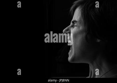 Depressed woman screaming to be heard, showing what it feels like living with Depression and Anxiety. - Stock Photo
