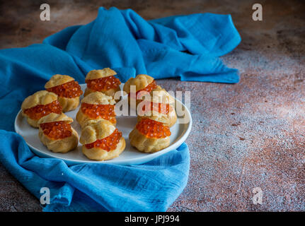 Homemade profiteroles stuffed with red caviar on white plate. Natural light, low angle, selective focus - Stock Photo