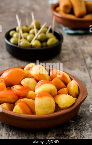 Traditional spanish tapas. Croquettes, olives and patatas bravas on wooden table - Stock Photo