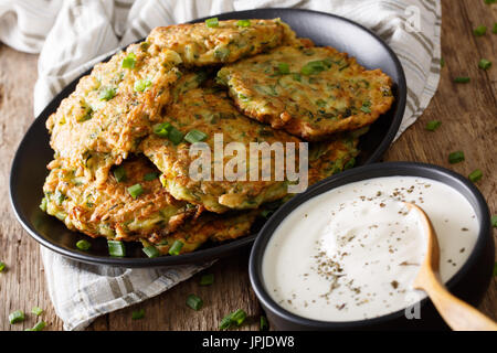 Delicious zucchini pancakes with sour cream close-up on the table. horizontal - Stock Photo