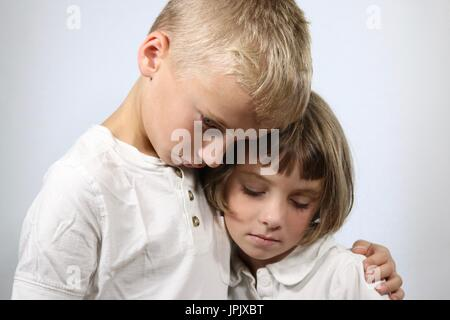 Portrait of grieving young children in an embrace - Stock Photo