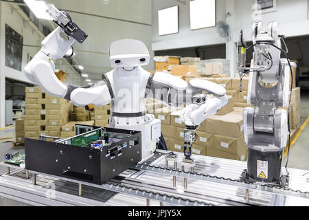 Industrial robot installing a computer chip in production line manufacturer factory, Controller of robotic arm for - Stock Photo