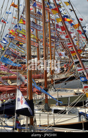 Brightly coloured bunting, flags and pennants flying from the masts of traditional wooden yachts old gaffers festival - Stock Photo