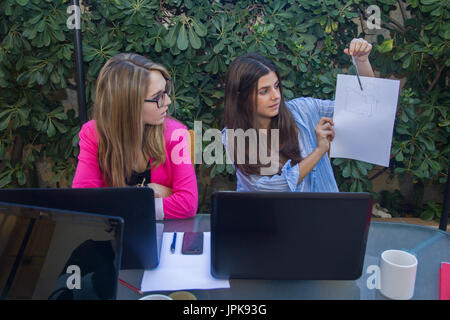 Young enterprising woman shows the other co-workers an outline on a white folio. She is explaining to them a project - Stock Photo