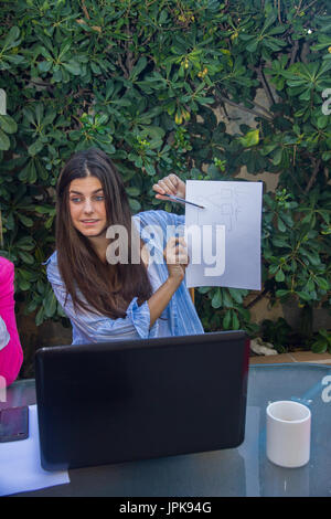 Young enterprising woman shows the other co-workers an outline on a white folio. She is explaining to them the project. - Stock Photo