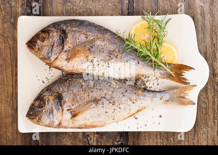 Delicious grilled sea bream fish on kitchen board with rosemary, lemon and colorful peppercorns on brown textured - Stock Photo