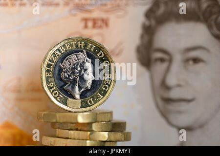 The new 12 sided one pound coin with a ten pound note in the background - Stock Photo