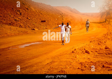 SENEGAL, AFRICA - APRIL 26 2016: Unidentified young Senegalese men walking home after working on a new road in Senegal. - Stock Photo