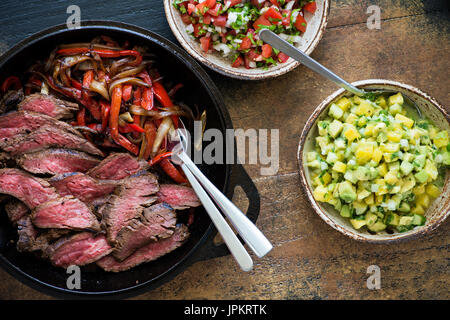 Homemade beef fajitas with bell peppers and onions served in cast iron skillet. Pico de Gallo salsa and guacamole - Stock Photo