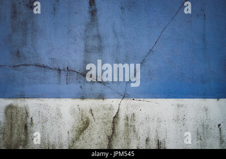 Cracked and grimy two-tone painted wall in Hove, East Sussex. - Stock Photo