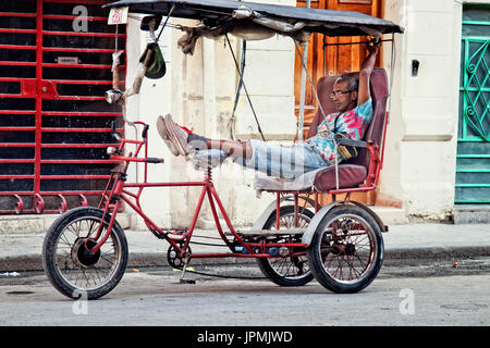 A man stretches out in his pedicab and waits for a passenger on a city street in Havana, Cuba. - Stock Photo