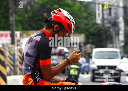 ANTIPOLO CITY, PHILIPPINES - JULY 30, 2017: A biker takes a break at a sidewalk and uses his smartphone. - Stock Photo