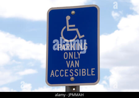 Handicap parking sign against blue sky with white fluffy clouds in background. - Stock Photo