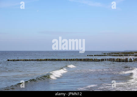 The waters of the Baltic Sea and many breakwaters form the seaside landscape in Kolobrzeg in Poland - Stock Photo