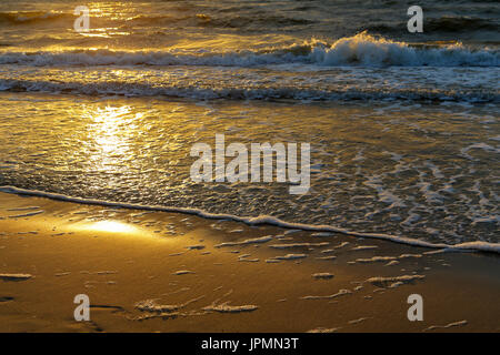 The rays of the sunset look at the gentle waves of the Baltic Sea which finally runs to the sandy beach of Kolobrzeg - Stock Photo