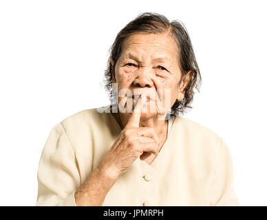 portrait of a senior woman smiling and whispering. Isolated on white background - Stock Photo