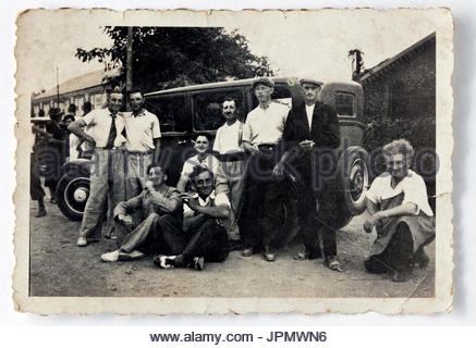 friends posing in front of a sedan car France 1930s - Stock Photo