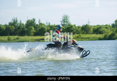 man on snowmobile goes fast on the water in summer - Stock Photo