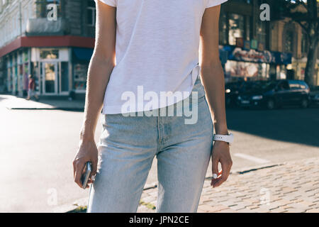 Details of women's clothing: a slender girl in jeans and a white T-shirt on the background of the city - Stock Photo
