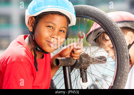 African boy repairing bicycle wheel with spanner - Stock Photo