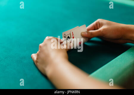 Player peeking cards in Blackjack game - Stock Photo