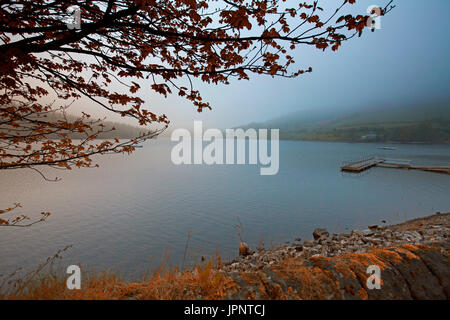 Landscape at Ladybower reservoir with blue sky and mist hovering over calm waters of lake and Ashopton viaduct in - Stock Photo