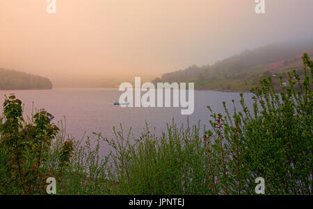 Landscape on misty morning at Ladybower reservoir with pink sunrise over calm waters of lake and Ashopton viaduct - Stock Photo