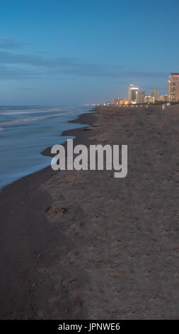 Portrait View of the Beach Shore with Beach Town in the background - Stock Photo