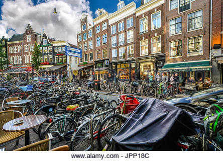 Busy and crowded street in downtown Amsterdam with shops, cafes and many bicycles - Stock Photo