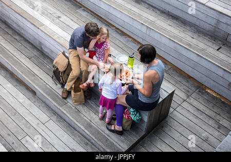 Young family on the High Line Park encouraging their two young girls to eat a takeaway lunch of stuffed pasta - Stock Photo