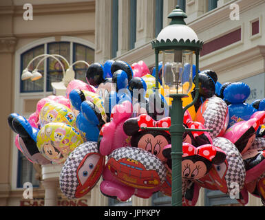 A bunch of colorful balloons with Minnie Mouse, Mickey Mouse and Cars with an old fashioned lamp post in the foreground. - Stock Photo