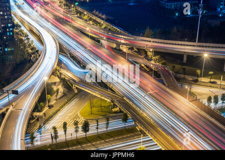 Car traffic on a flyover intersecting roads at night in Chengdu city - Stock Photo