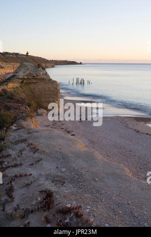 Looking down at the jetty ruins at Port Willunga, South Australia, during the golden hour, nearing sunset and at - Stock Photo