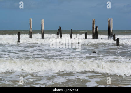Crashing waves and high tide at Port Willunga Beach, featuring the jetty ruins affectionately called the sticks - Stock Photo