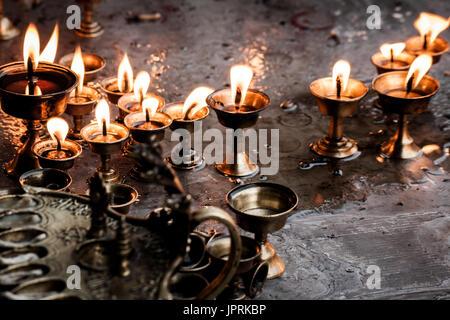 Collection of beautiful Hindu Oil Lamps burning at a Hindu Puja Ceremony in Kathmandu, Nepal. Devotional Hindu Oil - Stock Photo