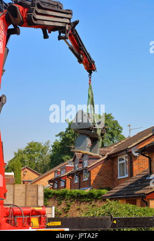 And out she comes, a large Henry Milnes Lathe is lifted from the rear of a property out througha gap between houses - Stock Photo