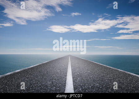 journey concept with long road with blue sea and blue sky - Stock Photo