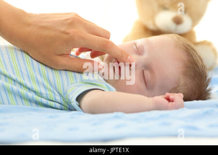 Mother hand touching the nose of a baby sleeping on a bed - Stock Photo