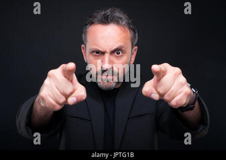 Furious classy man pointing at you with both index fingers on dark background - Stock Photo