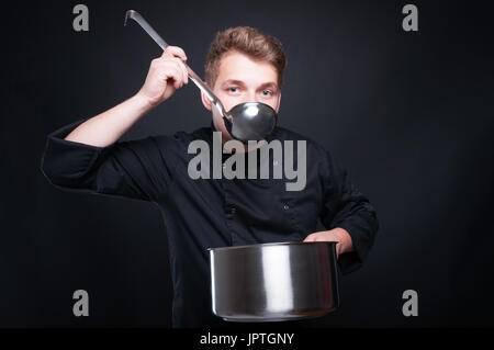 Male chef in uniform tasting his fresh soup from ladel on dark studio background - Stock Photo