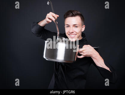 Happy chef man making delicious soup in silver pot isolated on black background - Stock Photo